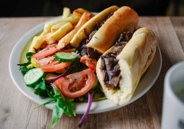 A roast beef baguette served with salad and chips at Chippenham Pit Stop
